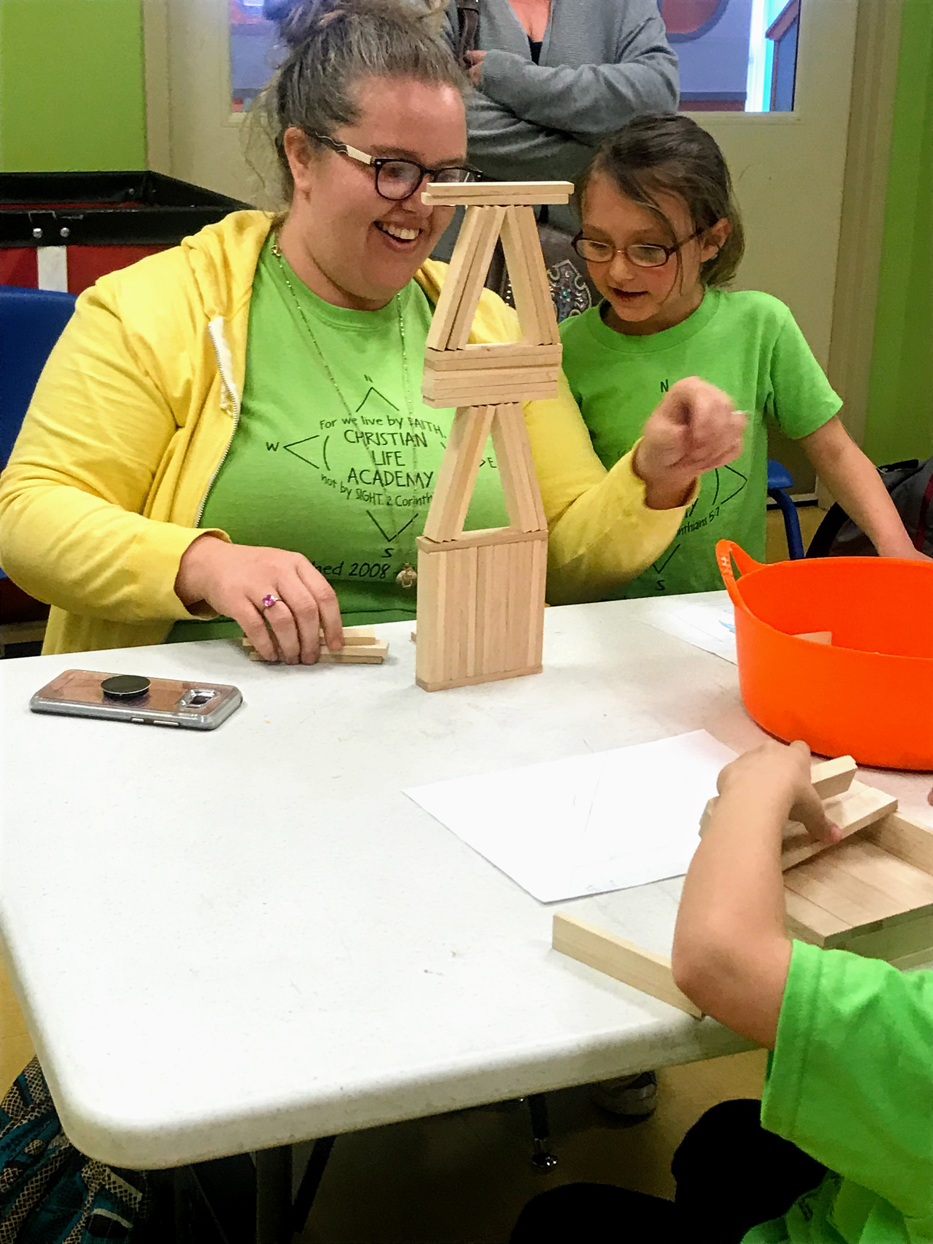 Teacher building with child